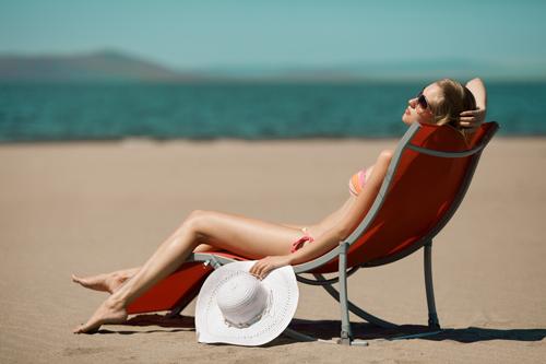 Beautiful-woman-lying-on-a-deckchair-at-the-beach